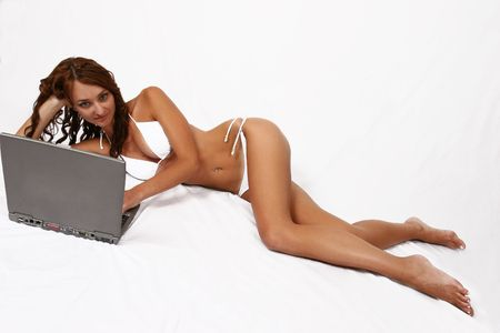 Woman in bikini laying on ground working on her computer photo