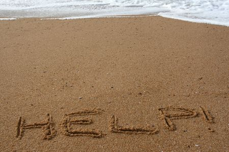 Word help spelled in the sand on a beach