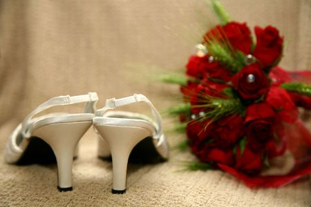 Pare of white shoes and rose bouquet photo