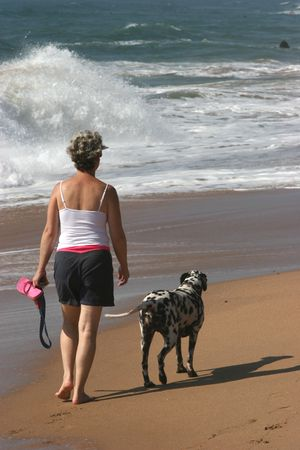 Woman walking with her dog on beach