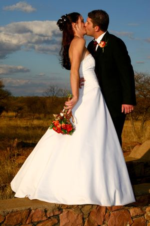 Bride and groom standing on stone wall photo