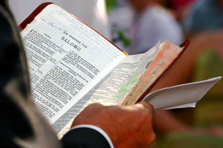Priest reading from the bible photo