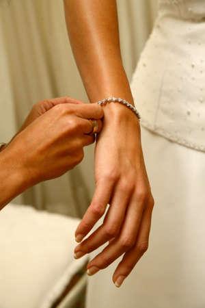Bridesmaid putting bracelet on brides arm Stock Photo