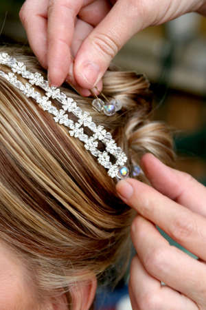 Hair stylist putting beads in brides hair for decoration Stock Photo