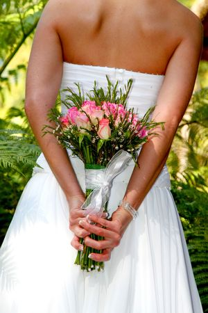 arm bouquet: Bride holding her pink rose bouquet behind her back