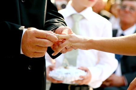 A groom putting a wedding ring on his brides finger photo