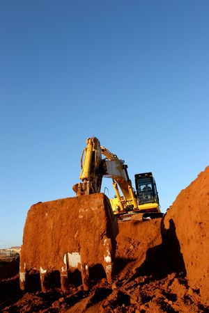 buildingsite: Heavy construction equipment digging into ground away Stock Photo