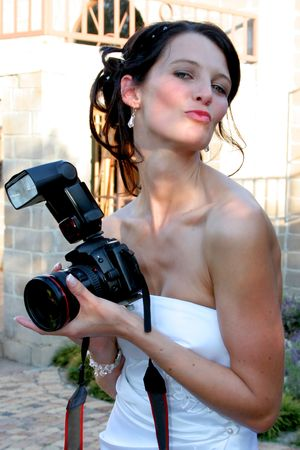 Bride playfully holding photographers camera and making kissing face