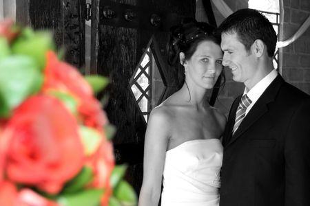 Bride and groom standing in chapel doorway next to hanging flowers Stock Photo - 604808