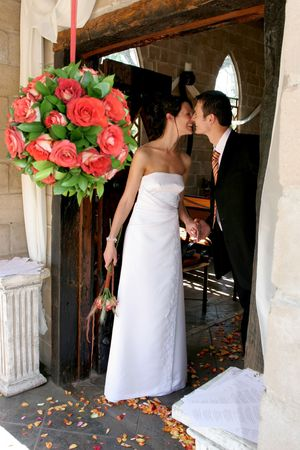 Bride and groom standing in chapel doorway next to hanging flowers
