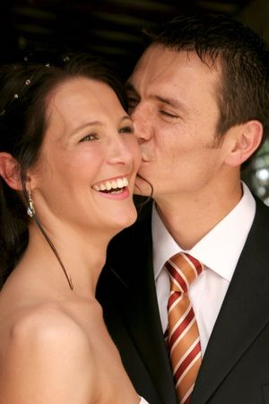 Bride smiling happy while groom give her a kiss Stock Photo - 604802