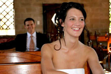 Bride and groom sitting on church benches photo