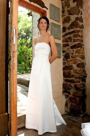 A bride in white wedding dress standing in a doorway