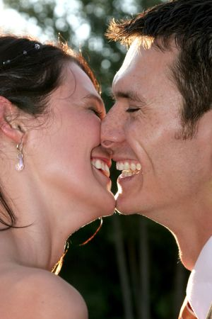 A couple on their wedding day kissing and laughing Stock Photo
