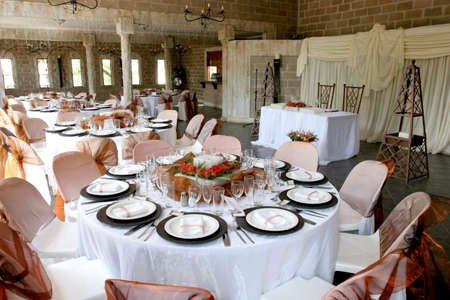 round chairs: A room decorated and tables set for a wedding reception