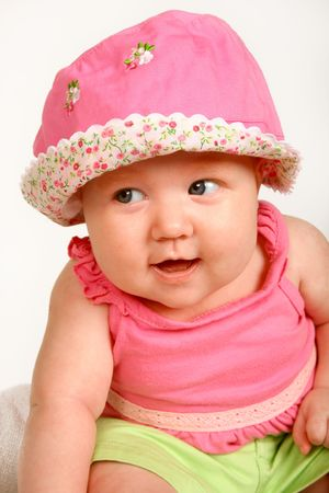A baby girl sitting with a hat on her head