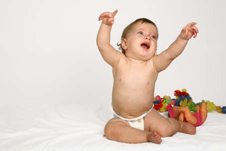 A baby girl holding her arms up and pointing