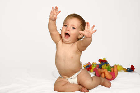A baby girl crying holding her arms up Stock Photo