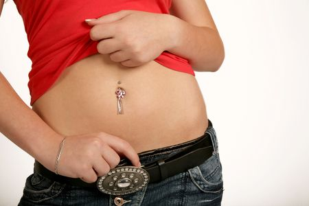 A woman standing showing her belly ring