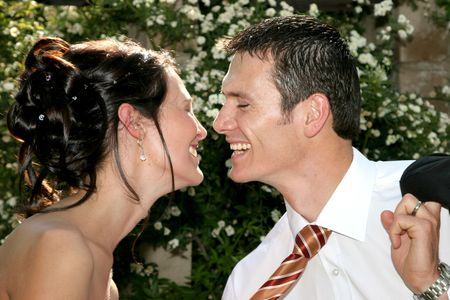 A bride pulling groom closer for a kiss photo
