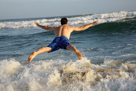 spread legs: A man jumping into the waves of the ocean Stock Photo