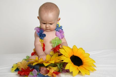 A little baby girl sitting in flowers photo