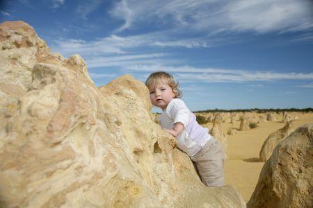 A little girl climbing on rocks