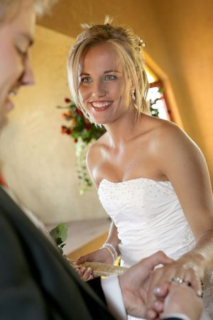 A Young bride having her weddingring put on photo