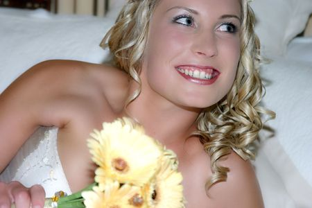Young bride on her wedding day, looking to the side and smiling photo