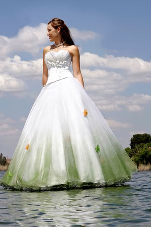 A bride standing next to river in her dress  Stock Photo