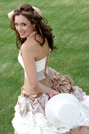 A bride standing on grass holding a hat Stock Photo