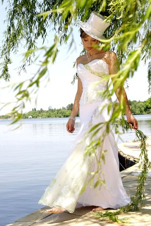 A bride standing between tree branches in her dress photo