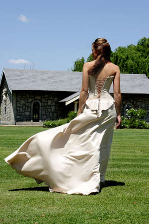 people from behind: A bride walking outside and wind blowing her dress   Stock Photo