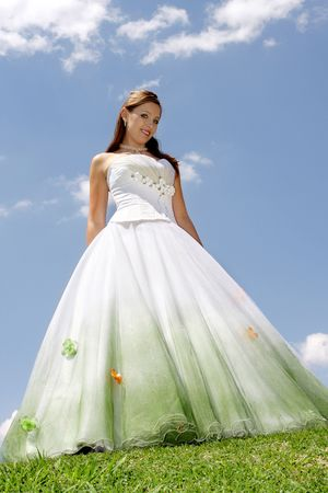 A bride standing in her dress on grass field