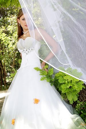 A bride standing outside in her wedding dress photo