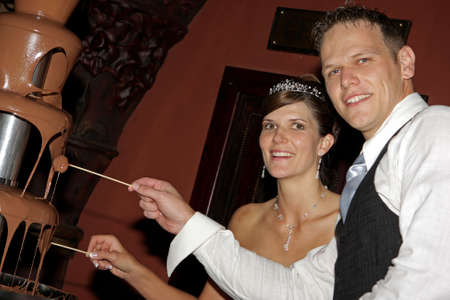 chocolate melt: A bride and groom eating from the chocolate fountain