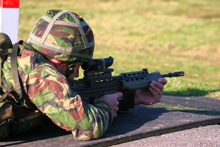 A Royal Navy sailor firing an SA80 assault rifle photo