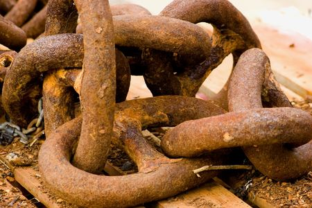 corroded: A group of large corroded chain links on a wooden crate