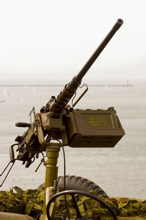 firepower: A large machine gun mounted on a military vehicle silhouetted against a busy harbour. Stock Photo