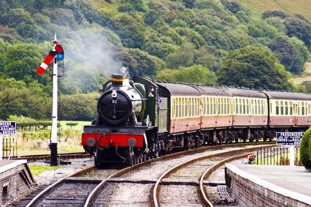 railway history: A steam train approaching the station on a preserved Victorian railway