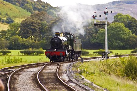 Steam engine approaching the station on a preserved Victorian railway photo