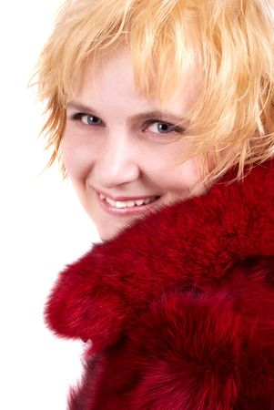 The beautiful blonde in a red fur coat. A portrait, studio shooting photo