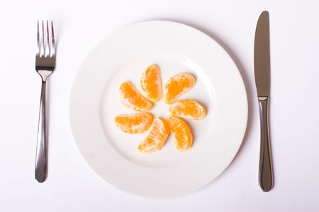 Orange mandarin on white plate with knife and fork, with soft shadow Stock Photo - 6519731