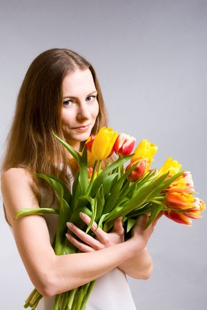 Beautiful young woman holding bouquet tulips