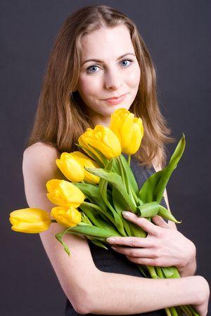 Beautiful young woman holding bouquet tulips photo