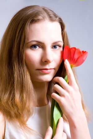 Beautiful young woman holding red tulip photo