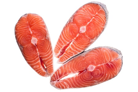 Three steak of raw salmon on a white background photo