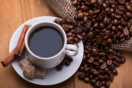 A cup of coffee with coffee beans and cinnamon sticks  photo