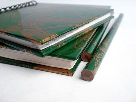 green notepad with diary and two pencils on a white background photo