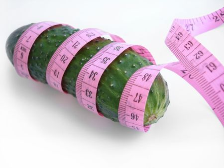 scrawny: cucumber with pink tape measure over white background Stock Photo